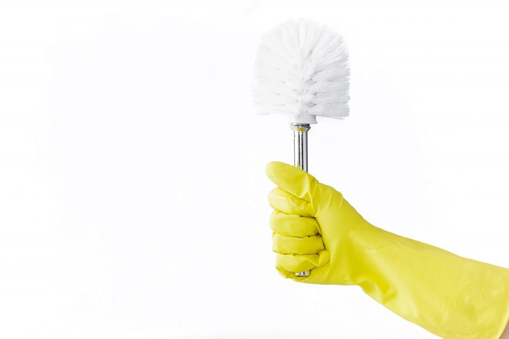 Hand in a rubber yellow glove holds brush for the toilet  on a white background. cleaning.